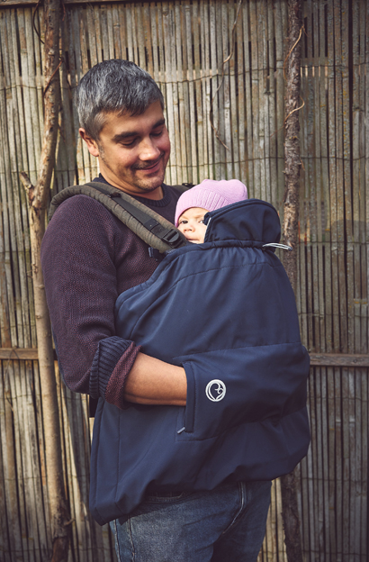 A man carrying his baby in a brown buckle carrier using the Mamalila Softshell Babywearing Cover in Navy to cover the carrier
